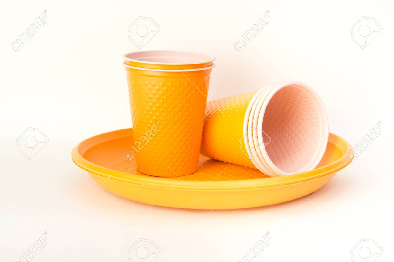 Plastic granules and disposable tableware made of polyethylene, polypropylene polymeric material on a white background. BPA FREE - 150324335