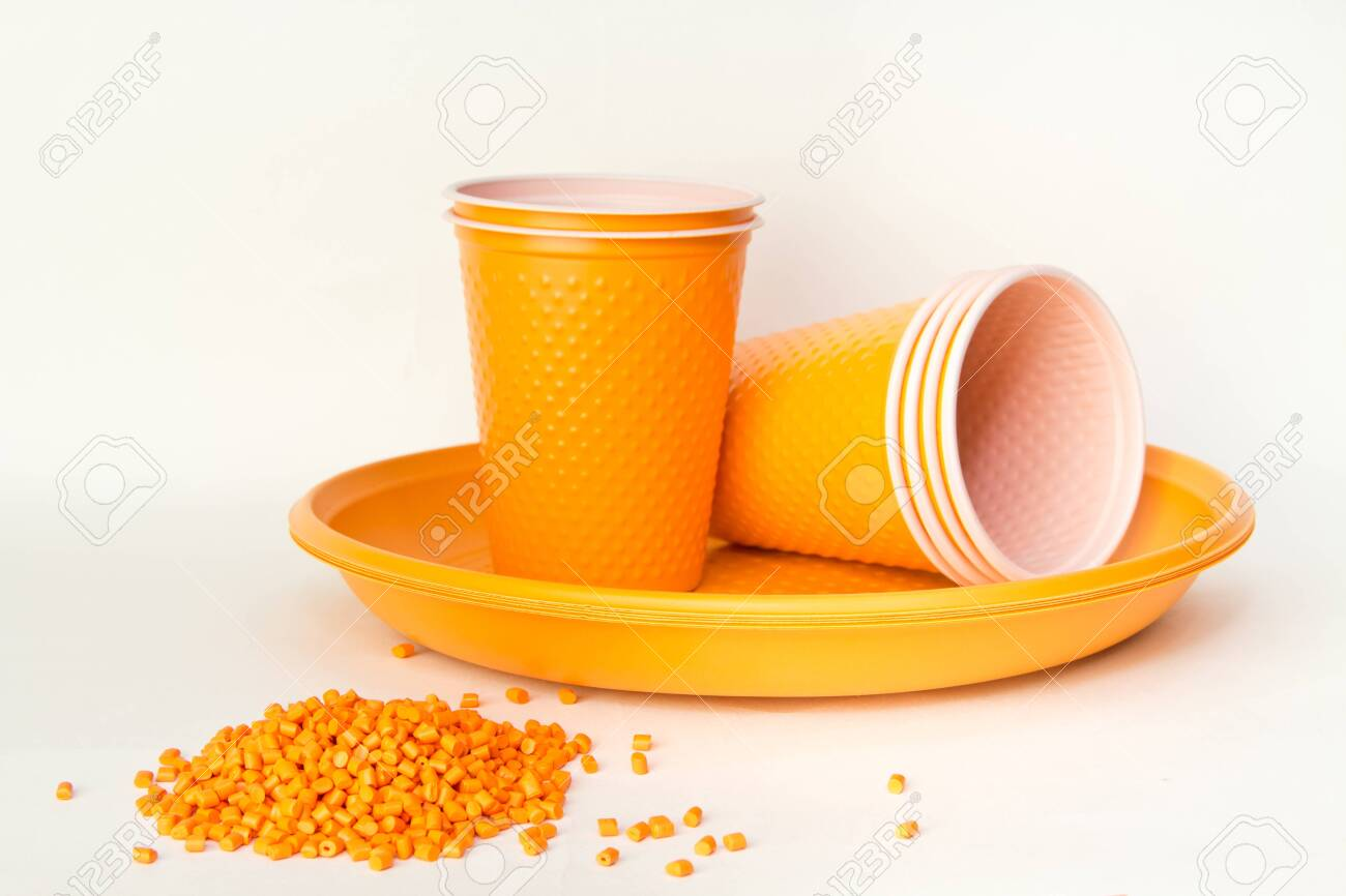 Plastic granules and disposable tableware made of polyethylene, polypropylene polymeric material on a white background. BPA FREE - 150324337