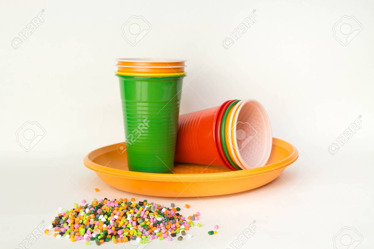 Plastic granules and disposable tableware made of polyethylene, polypropylene polymeric material on a white background. BPA FREE - 150324339