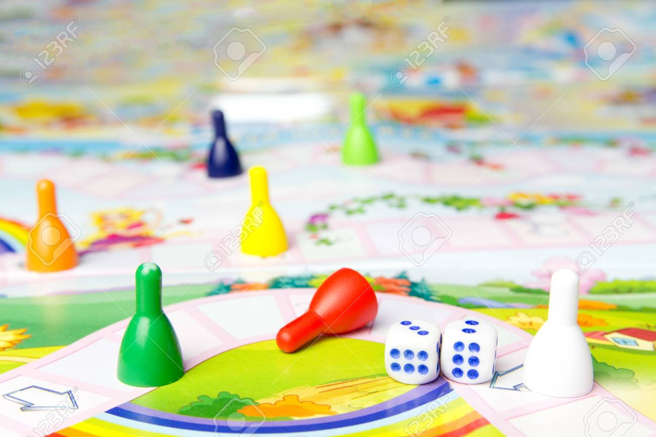Board games for the home. Yellow, green, blue, red plastic chips and dice on Board games for children . Selective focus - 150324355
