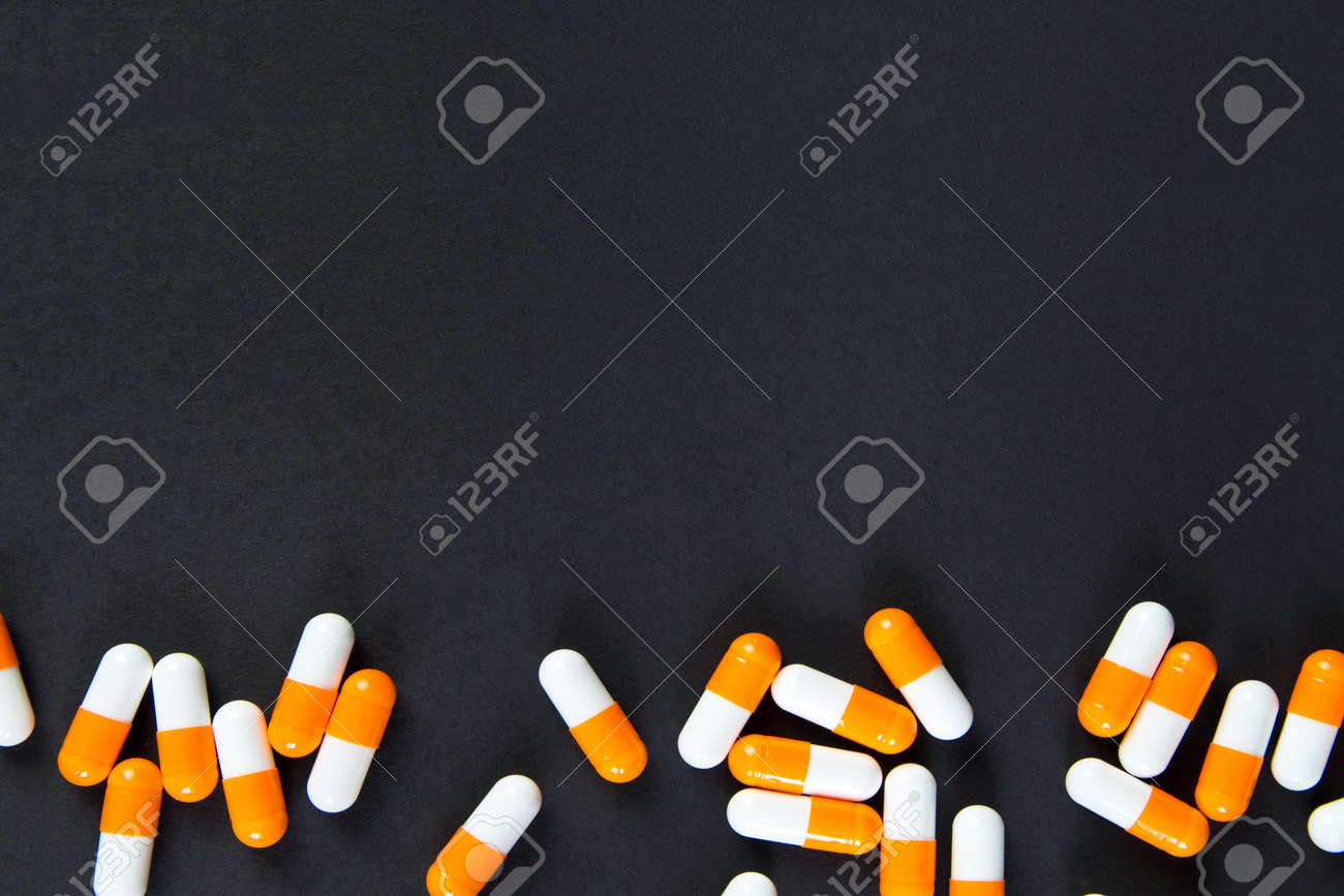 Capsules (pills) orange and white were posted in the black background with copy space. Medical background, template.Pattern , Identification of pills - 150324369
