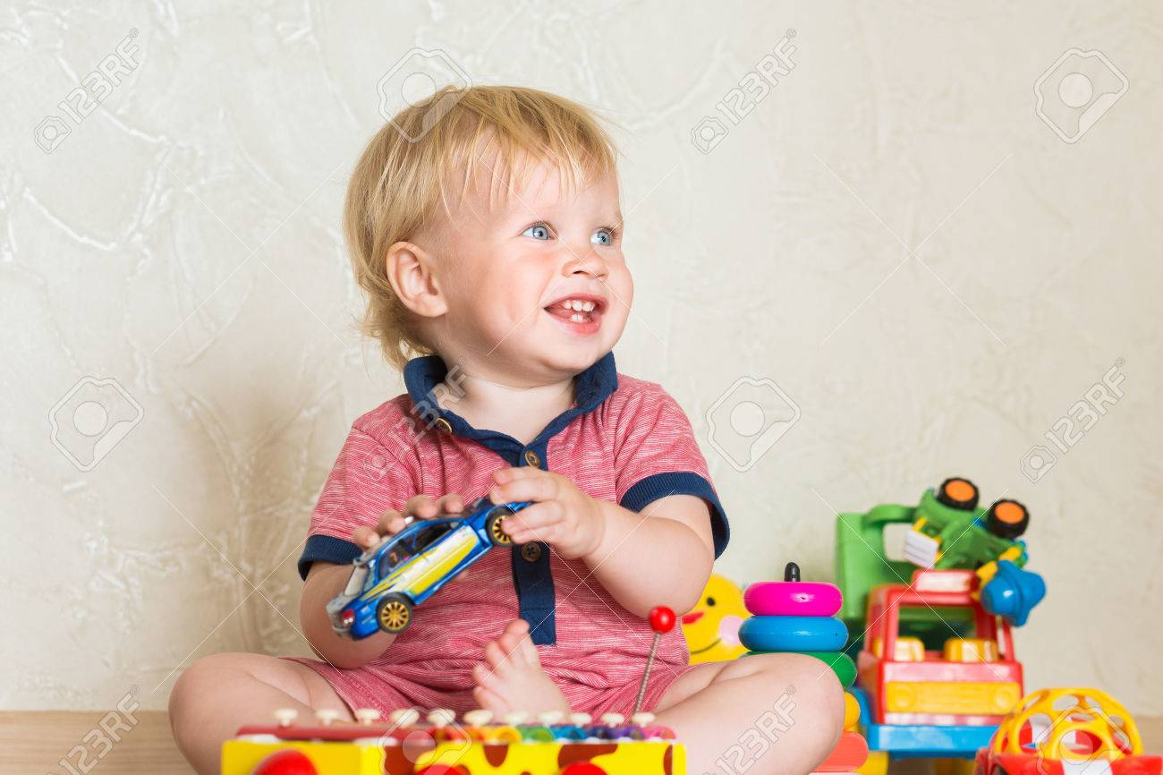 Portrait Of A Beautiful Baby Boy On The Floor With Car Toys Stock