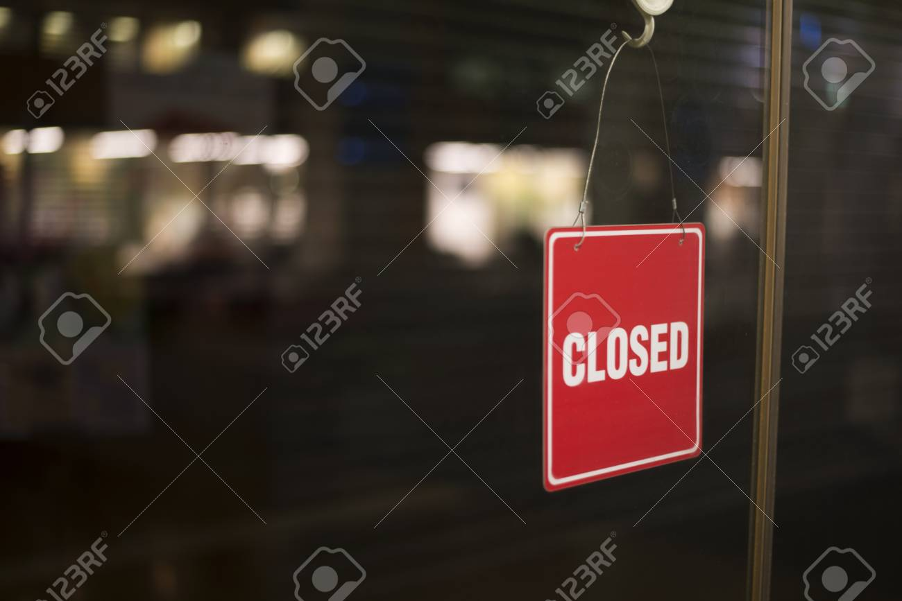 Shot Of A Red Color Closed Sign Hanging From Inside A Glass Sliding