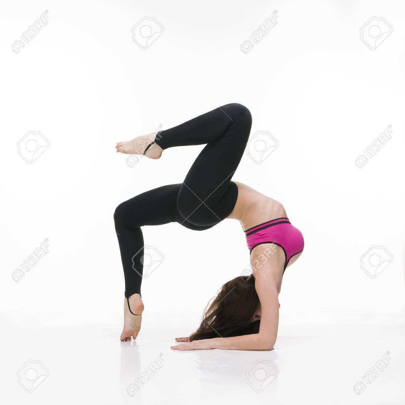 94686f8715 Stock Photo - Young beautiful caucasian woman in yoga pose in studio on  white background. Sexy female body