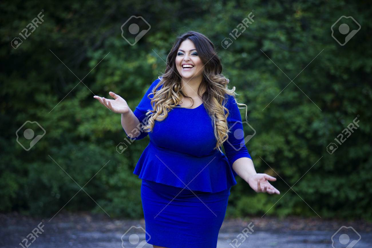 9820a83ca0566 Young happy smiling beautiful plus size model in blue dress outdoors