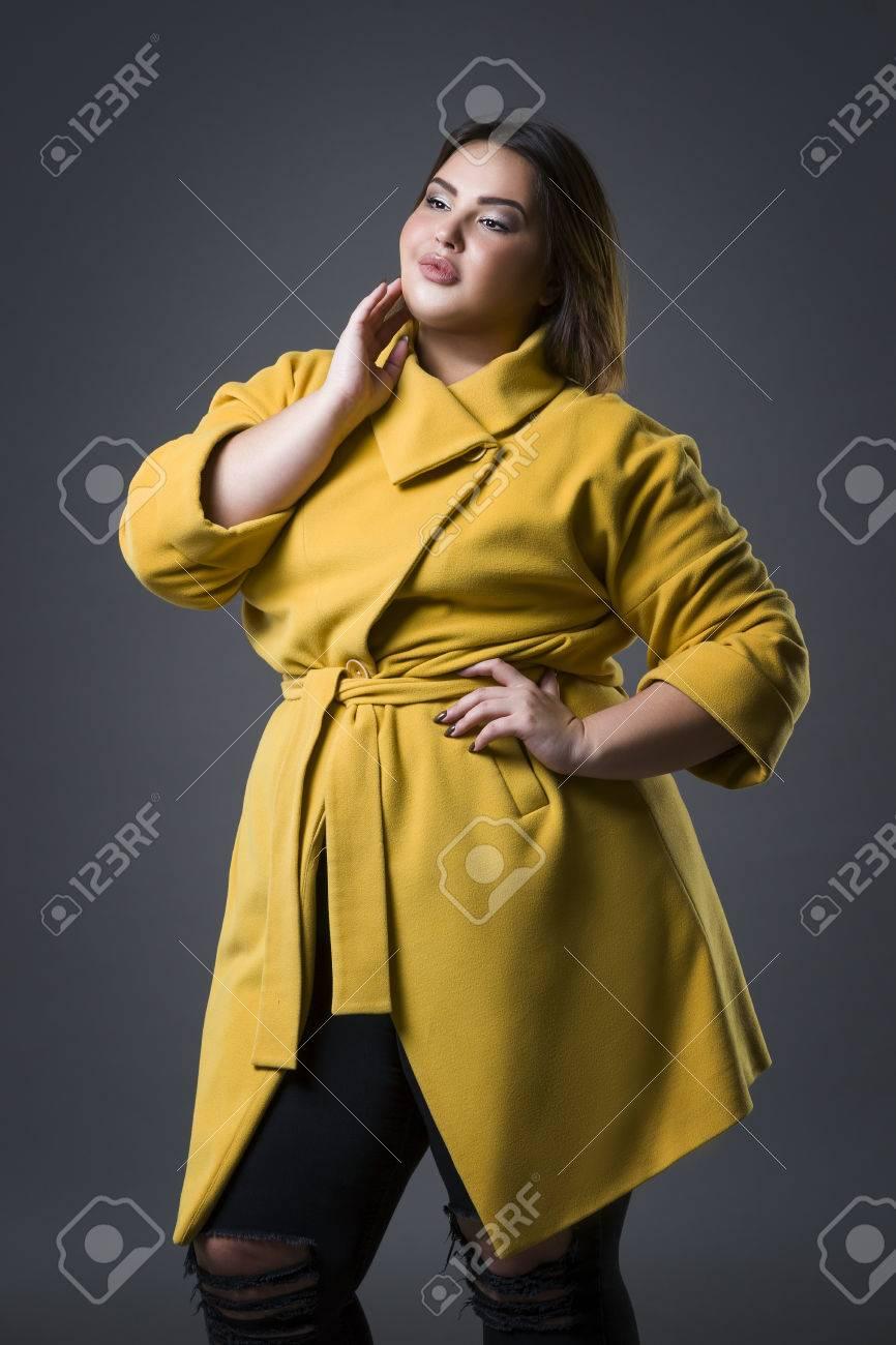 huge selection of 6fb30 df63f Modello di moda di dimensioni più grande in cappotto giallo e cappello  nero, donna grassa su sfondo grigio dello studio, sovrappeso corpo femminile