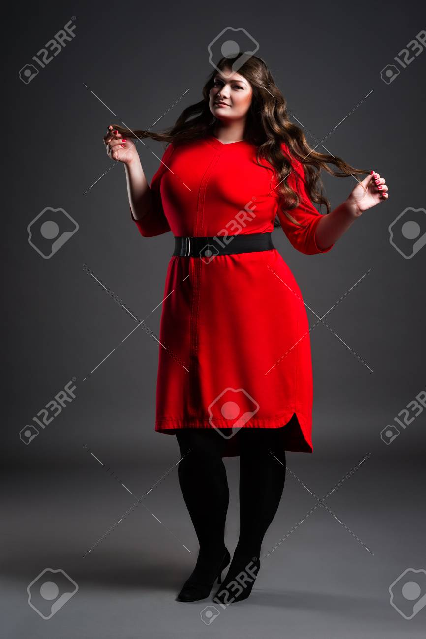 Plus size fashion model in red dress, fat woman on gray studio..