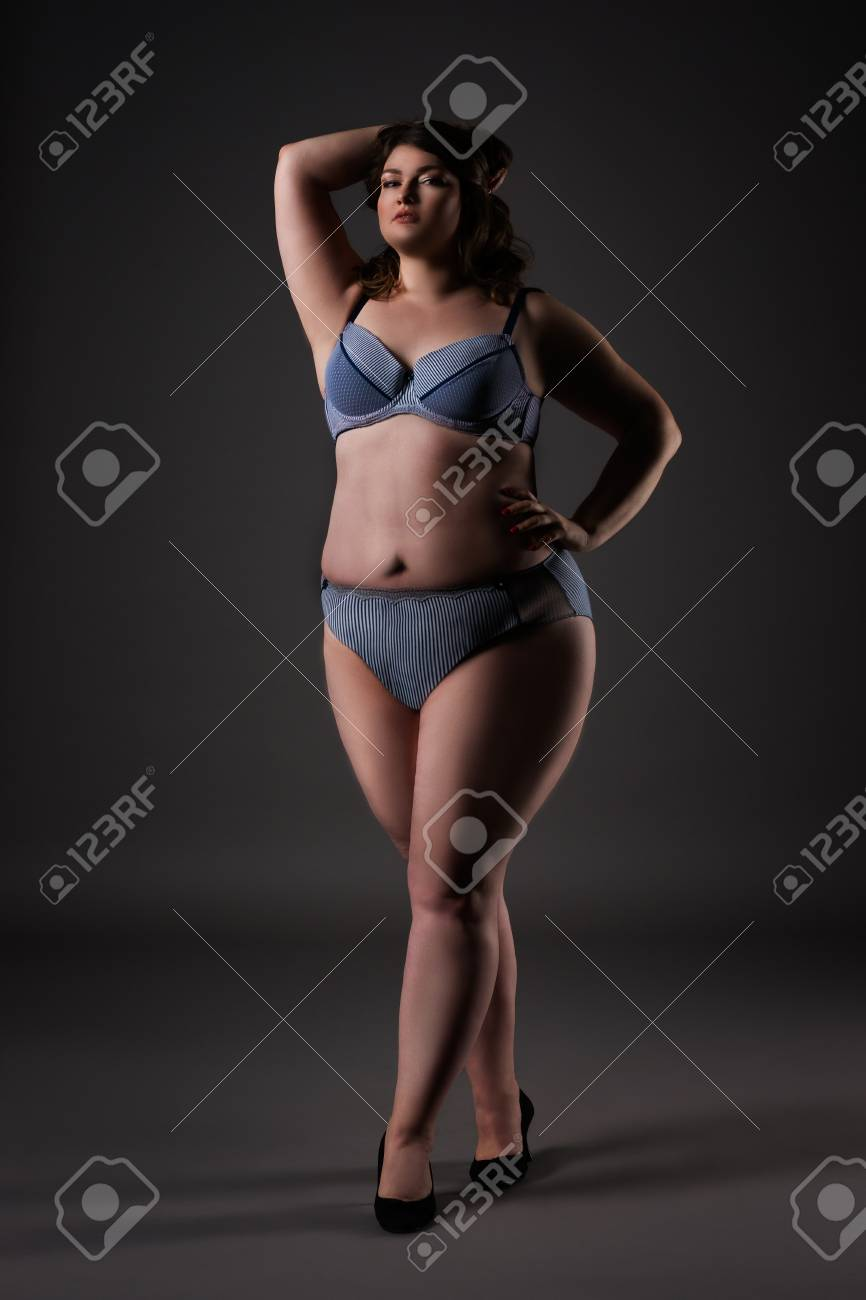 Plus size sexy model in underwear, fat woman on gray studio background,  overweight female