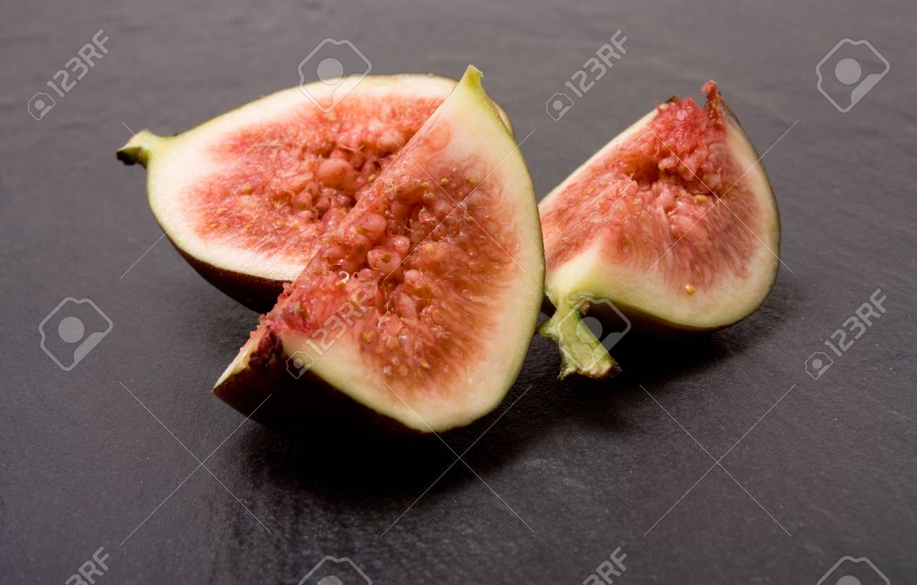 Close up of Sliced ripe figs from low viewpoint  against dark slate background. Stock Photo - 6686707