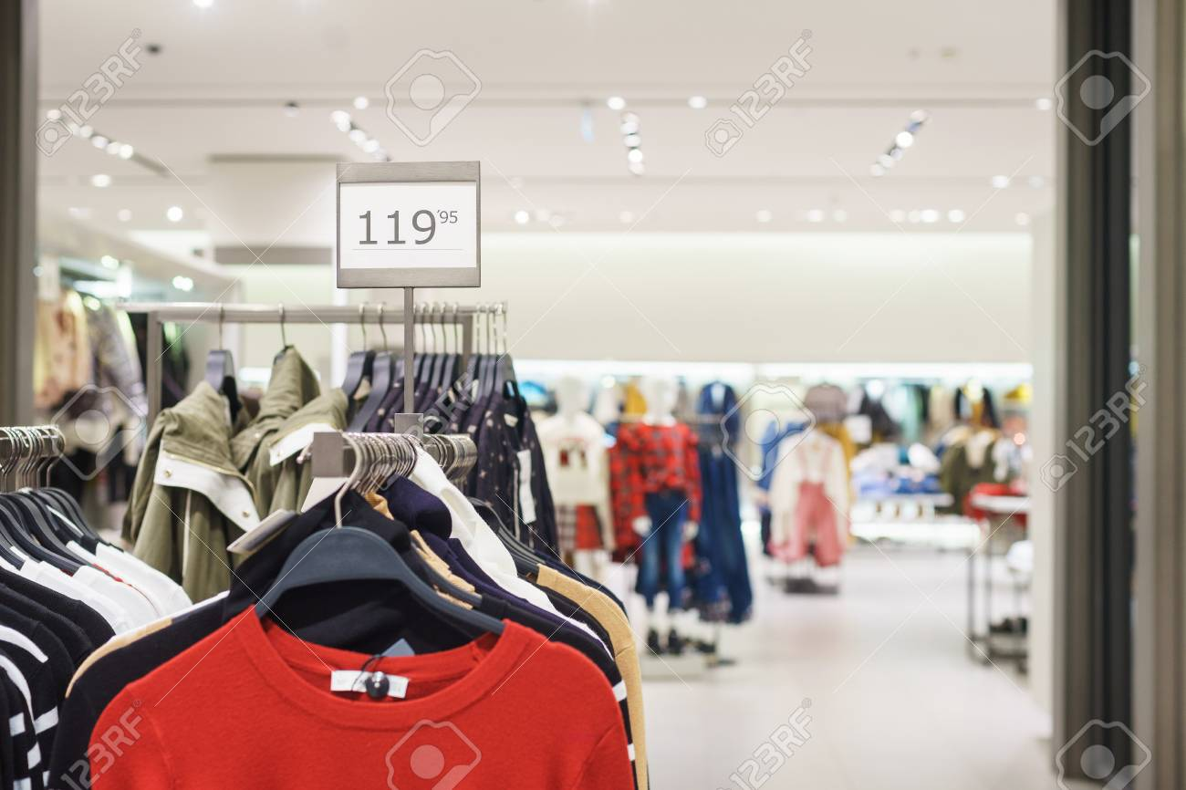 1e3bebbf9336 Fashionable men's and women's clothing on wooden hangers in a modern clothing  store. Stylish clothes