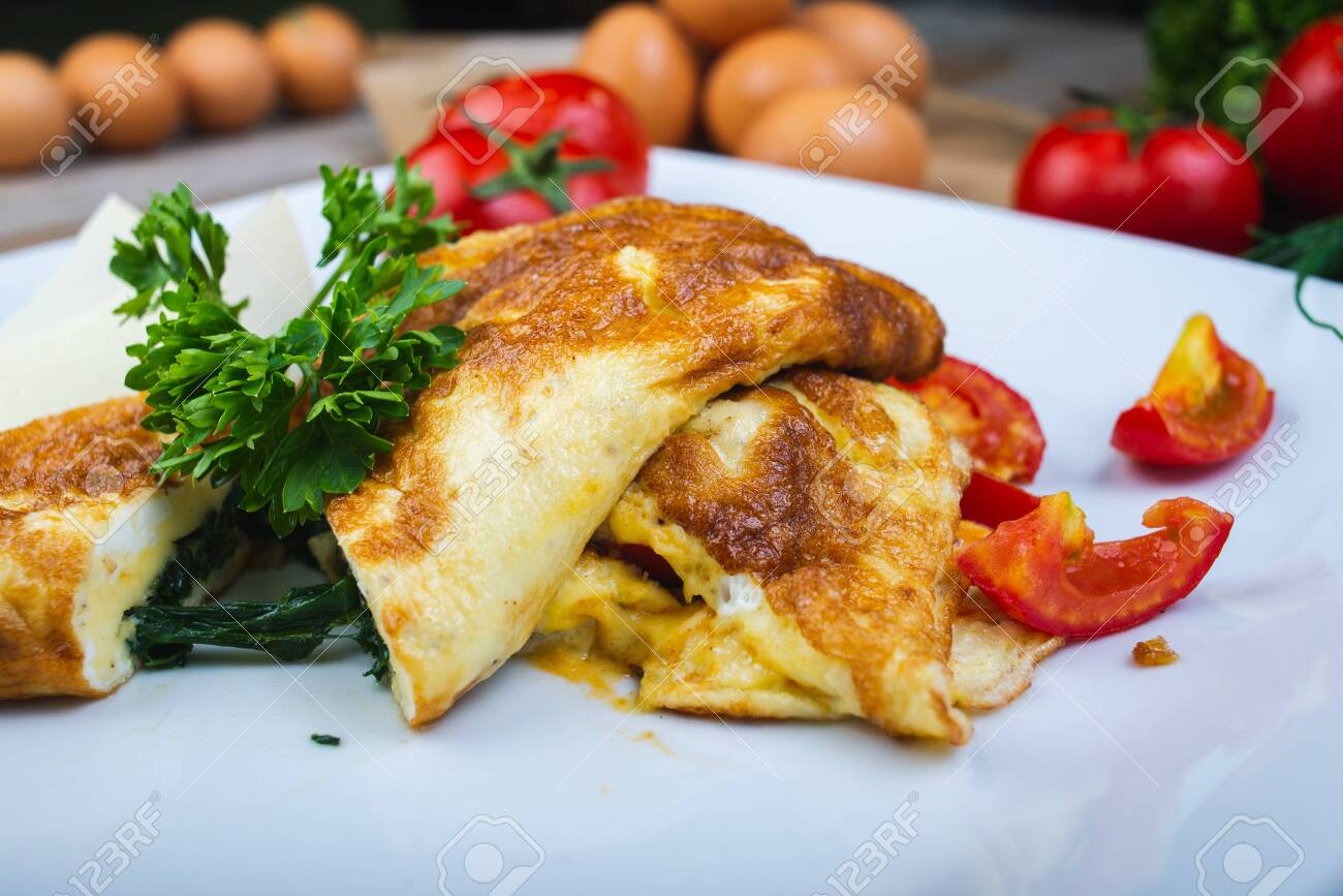 Traditional omelet with vegetables, spinach, tomatoes and herbs on a wooden table in a restaurant. Classic european breakfast. Fried eggs with milk and cheese. Soft focus. - 140115253