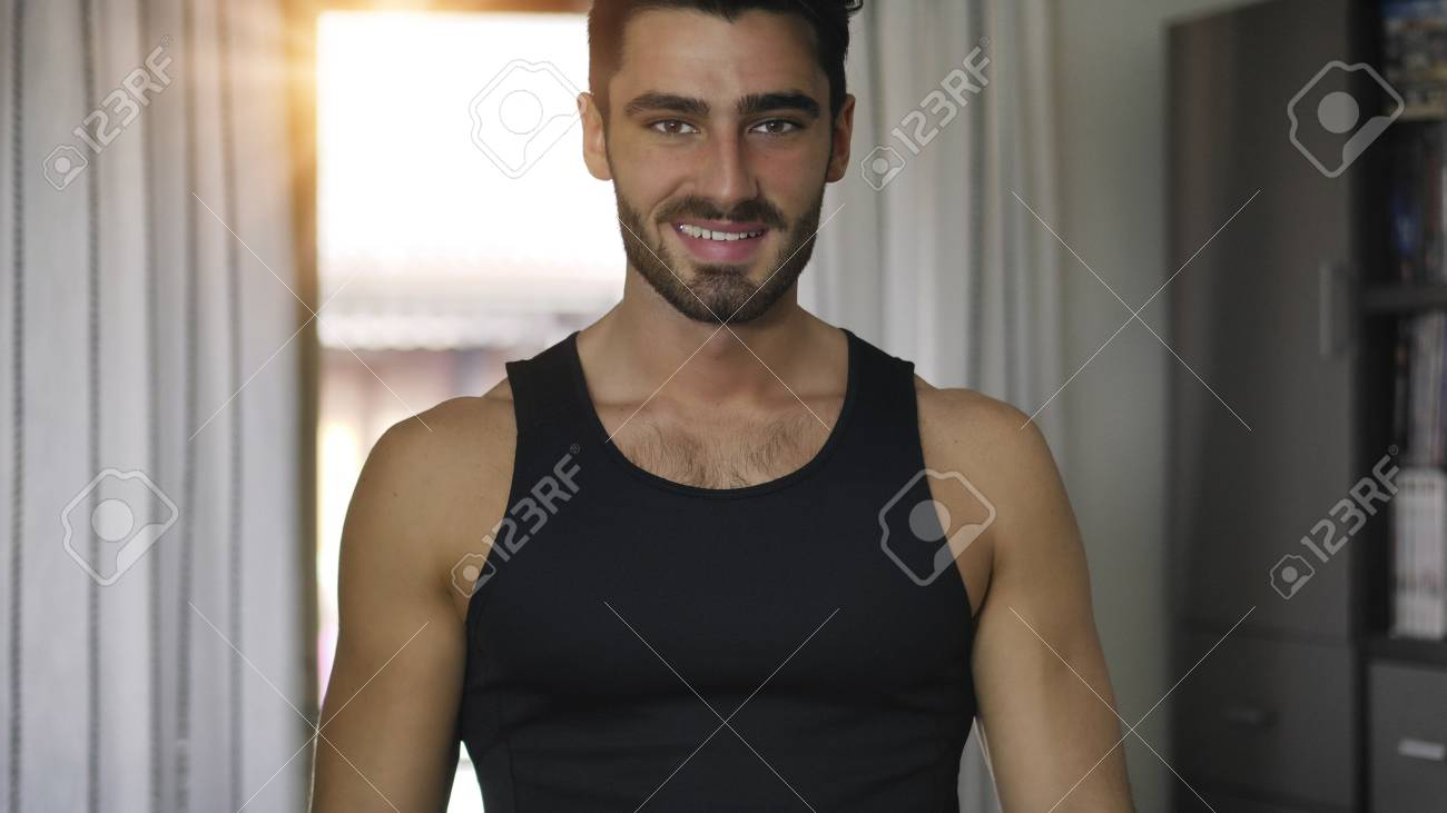 367575c4c Stock Photo - Young handsome man at home smiling to camera, wearing black  tank-top