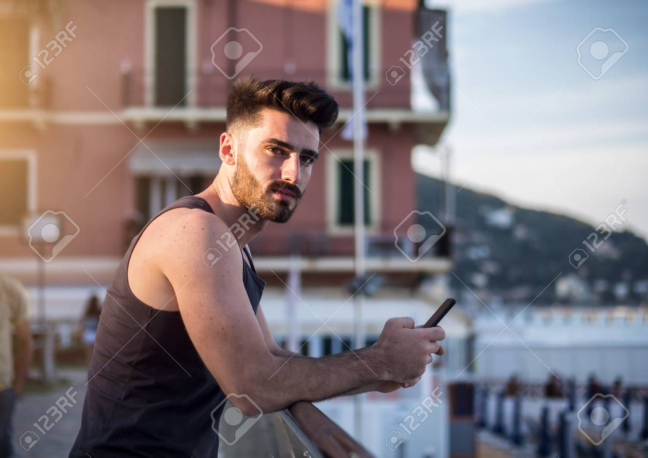 bf30d946e82ad Attractive fit athletic young man at sunset on seaside boardwalk or  seafront