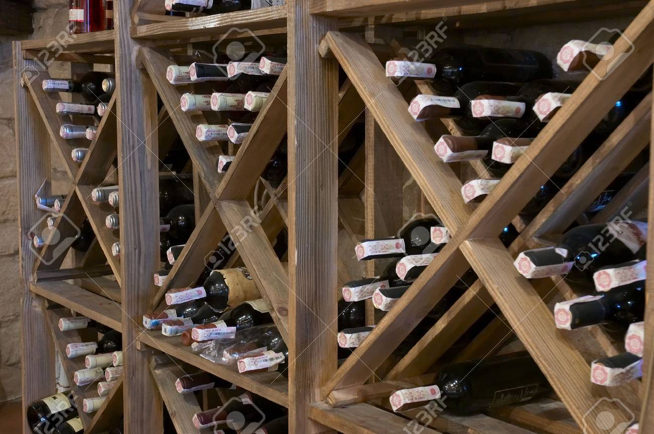 wine bottles laying in wooden rack Stock Photo - 574328