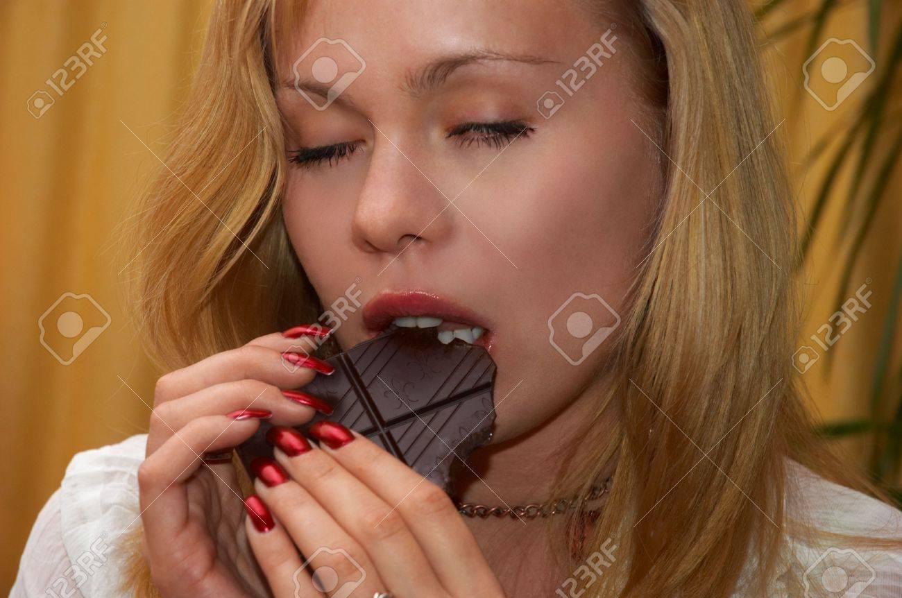 attractive blonde blonde girl eating dark chocolate Stock Photo - 592712