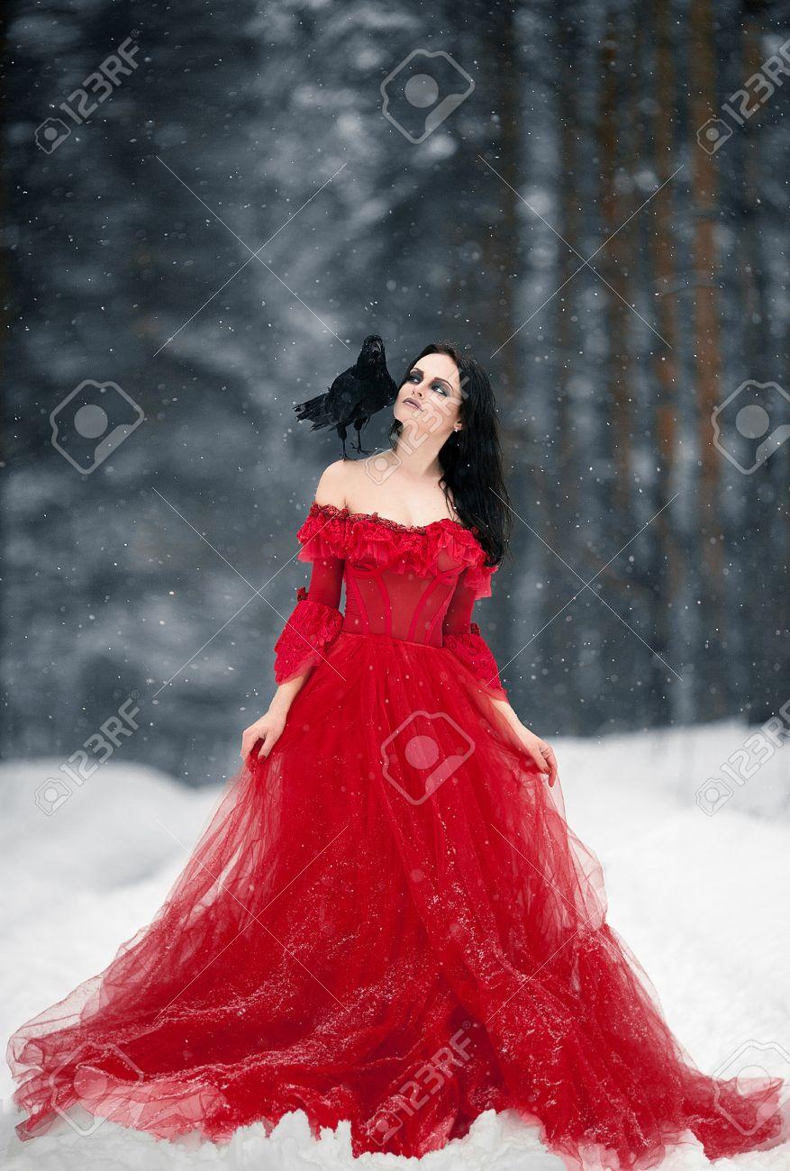 45af077ea8e Sorcière Femme En Robe Rouge Et Le Corbeau Sur Son épaule Dans La Forêt  Enneigée. Sa Longue Robe Couché Sur La Neige Et Elle Regarde Le Corbeau.