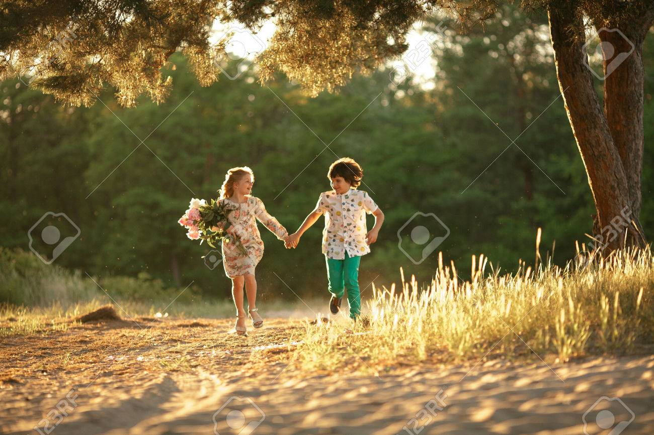 Little Girl With Bouquet And Boy Are Running In Sunny Forest Stock