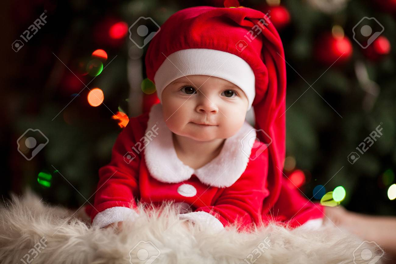 0836df1492f64 Cheerful baby girl in Santa Claus costume and hat lies on fur rug against  background of