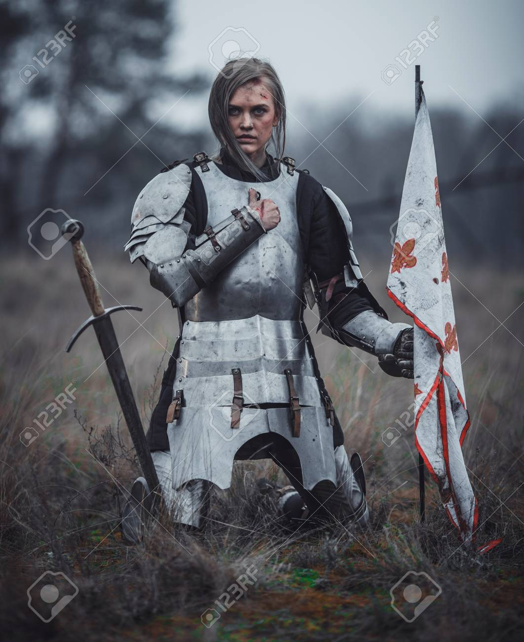 girl in armor kneels with flag in her hands and sword on meadow