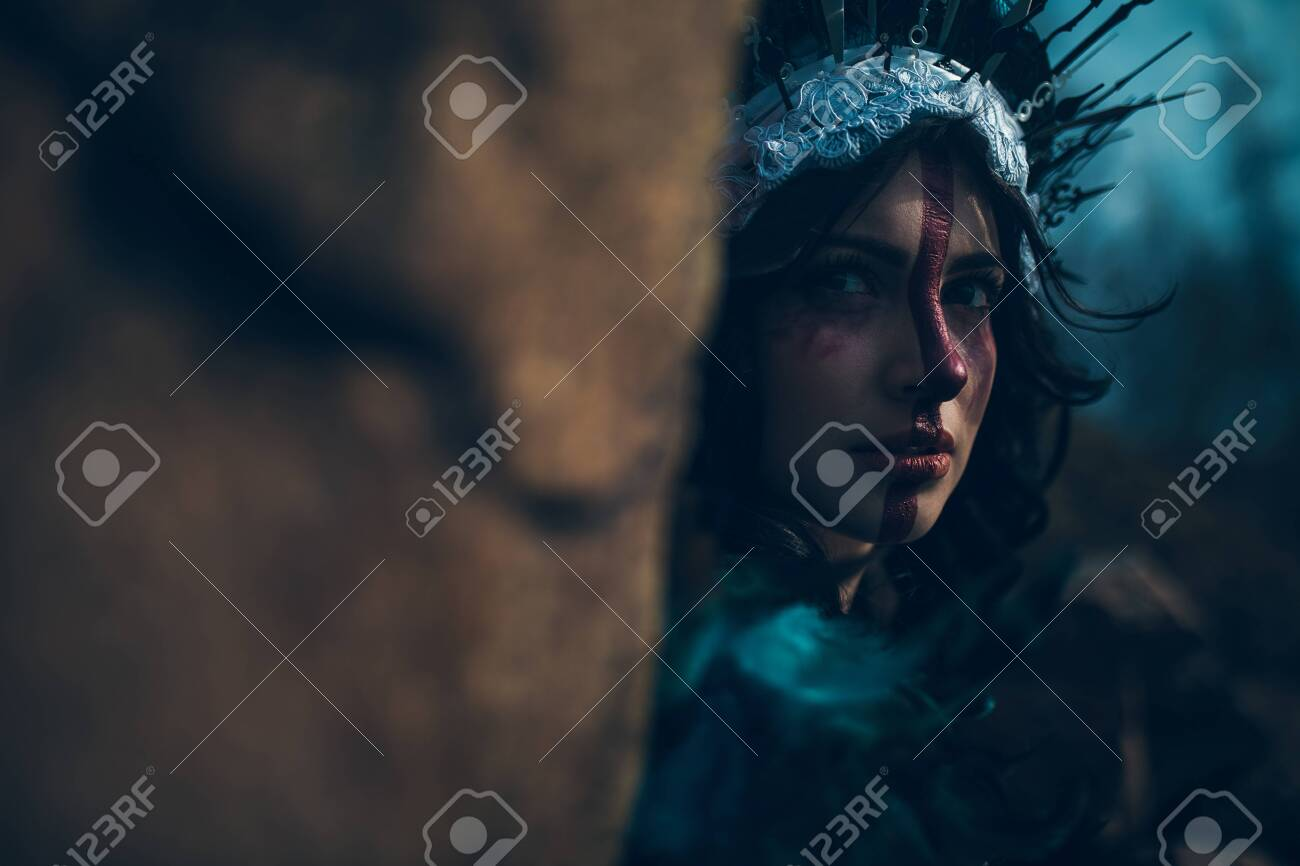 Portrait of young woman in the image of a fairy and a sorceress standing next to the rock in a black dress and a crown. - 120542024