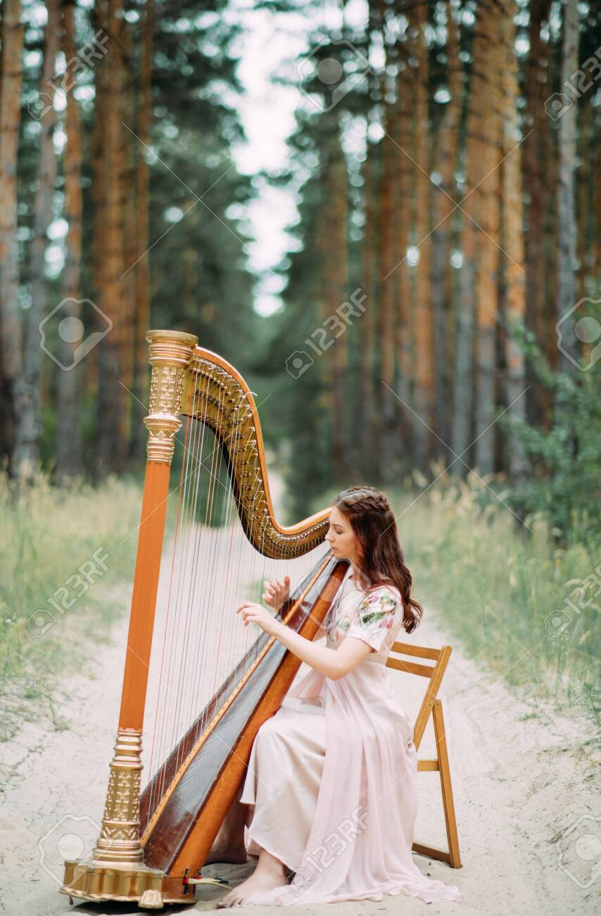 https://previews.123rf.com/images/stasia04/stasia041908/stasia04190800168/129447501-woman-harpist-sits-at-forest-road-and-plays-harp-in-beautiful-dress-against-a-background-of-pines-.jpg