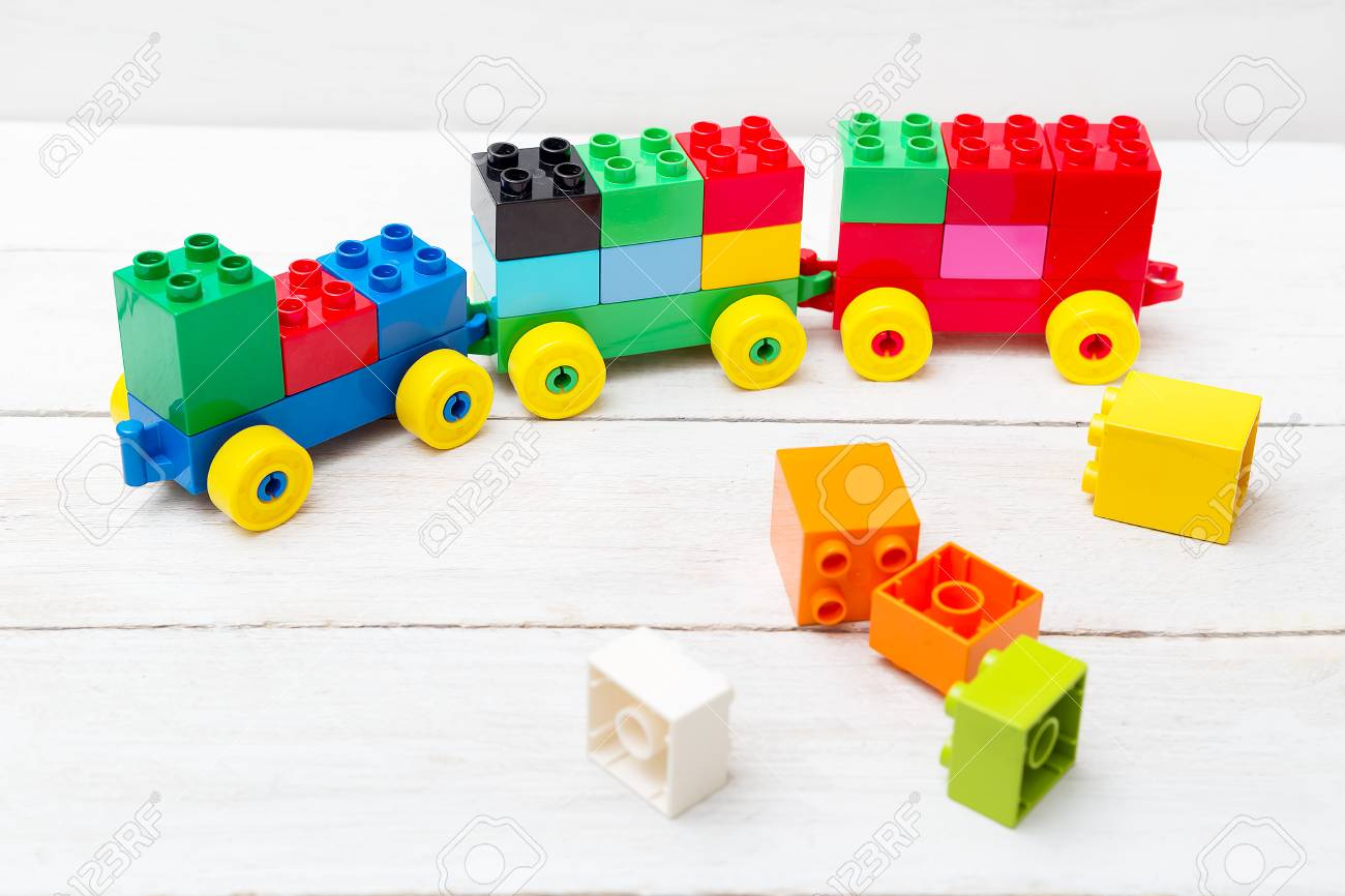 a toy train of cubes of lego on a wooden background. educational..