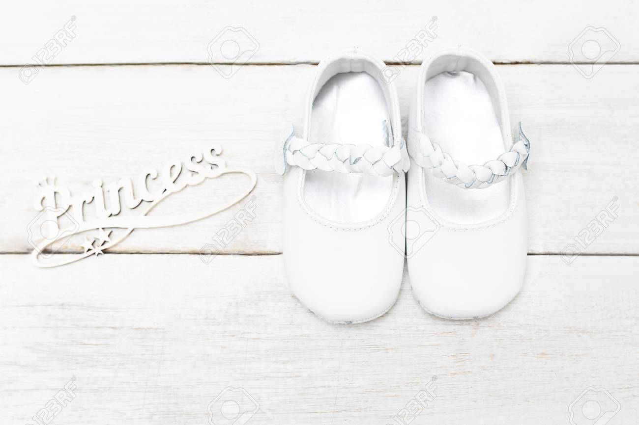 Shoes For A Little Girl Of White Color And The Inscription Of