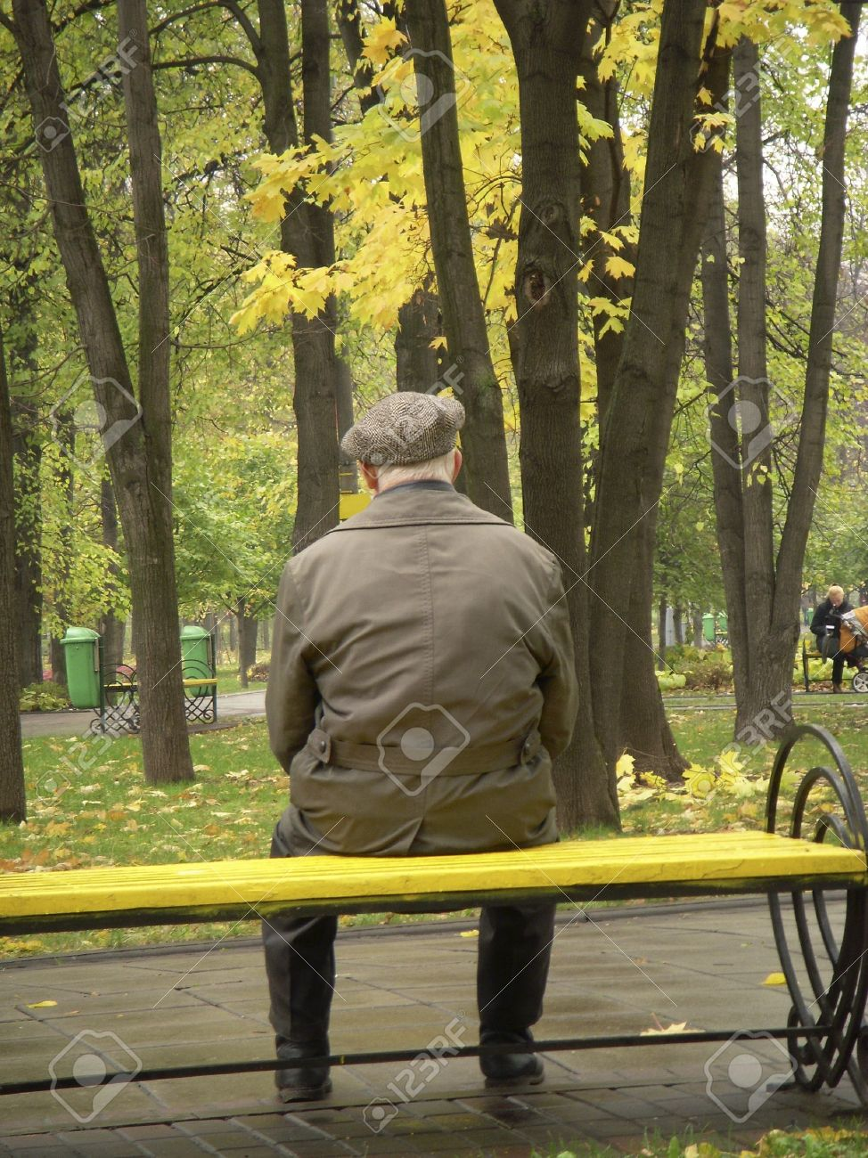 A Lonely Old Man Sitting On A Bench In A Park In Moscow Among