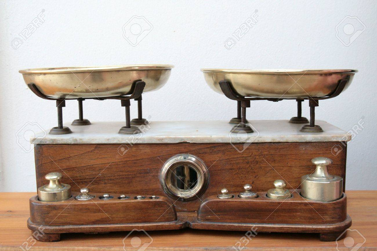 antique scale with brass pans and weights and a wood and marble