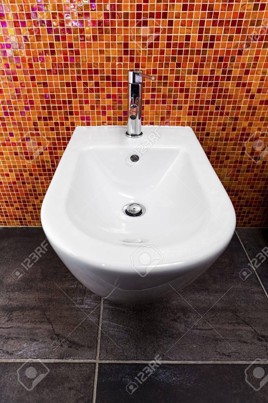 Bidet installé dans une salle de bain avec un mur de mosaïque de tons  chauds et un sol gris foncé