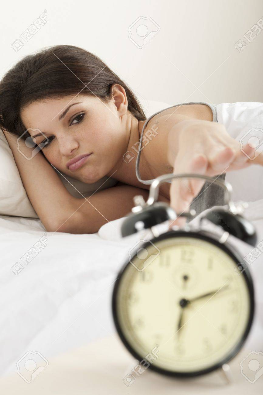 Young woman waking up in the morning , trying to put off an alarm clock Stock Photo - 7149717