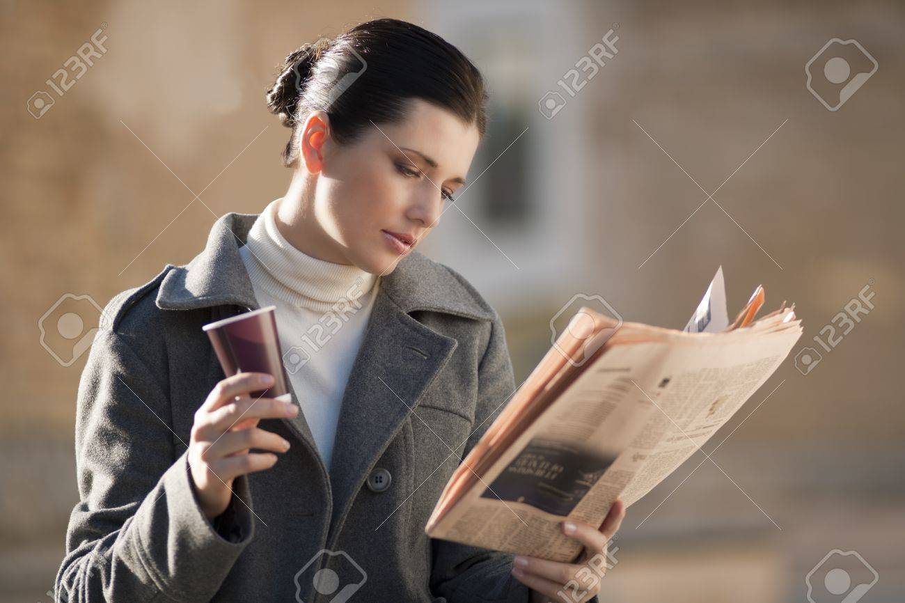 Young businesswoman taking a rest with newspaper and coffee Stock Photo - 8021973