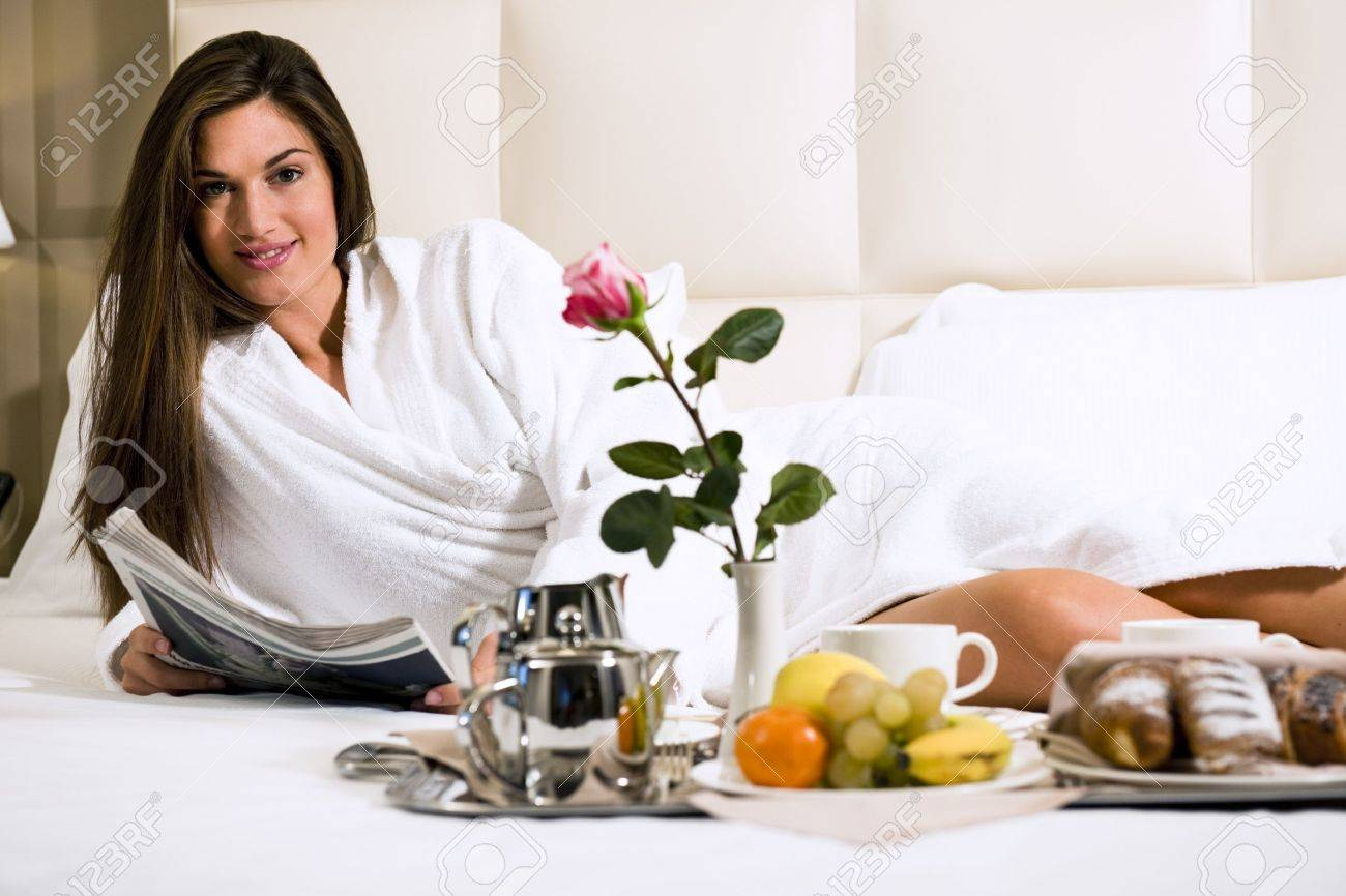Relaxed Woman Having Breakfast in Bed, home or hotel room Stock Photo - 9260263