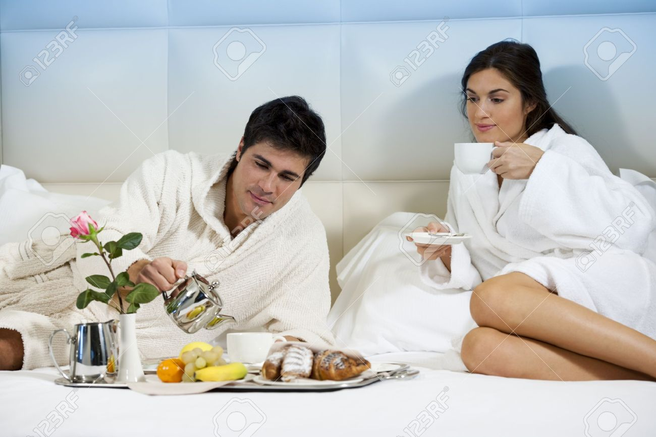 Relaxed Couple in Bed, hotel room - 9260335
