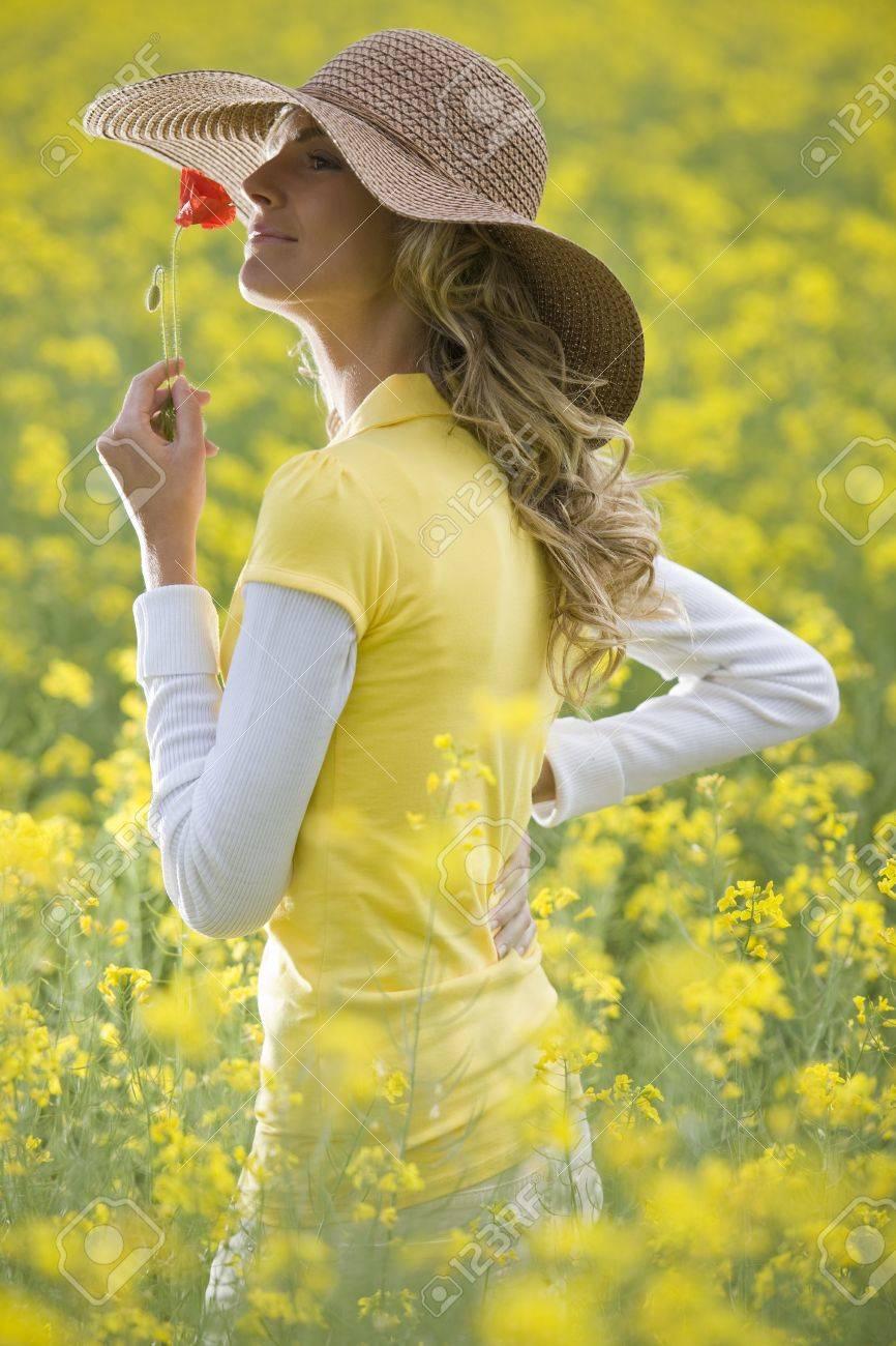Beautiful woman holding a poppy flower in a field Stock Photo - 9864972