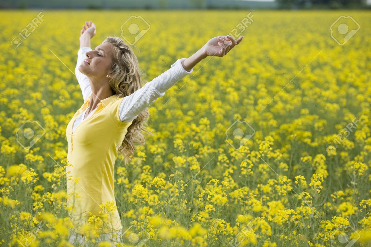 Beautiful woman in a yellow flowers field with arms outstretched Stock Photo - 9864971
