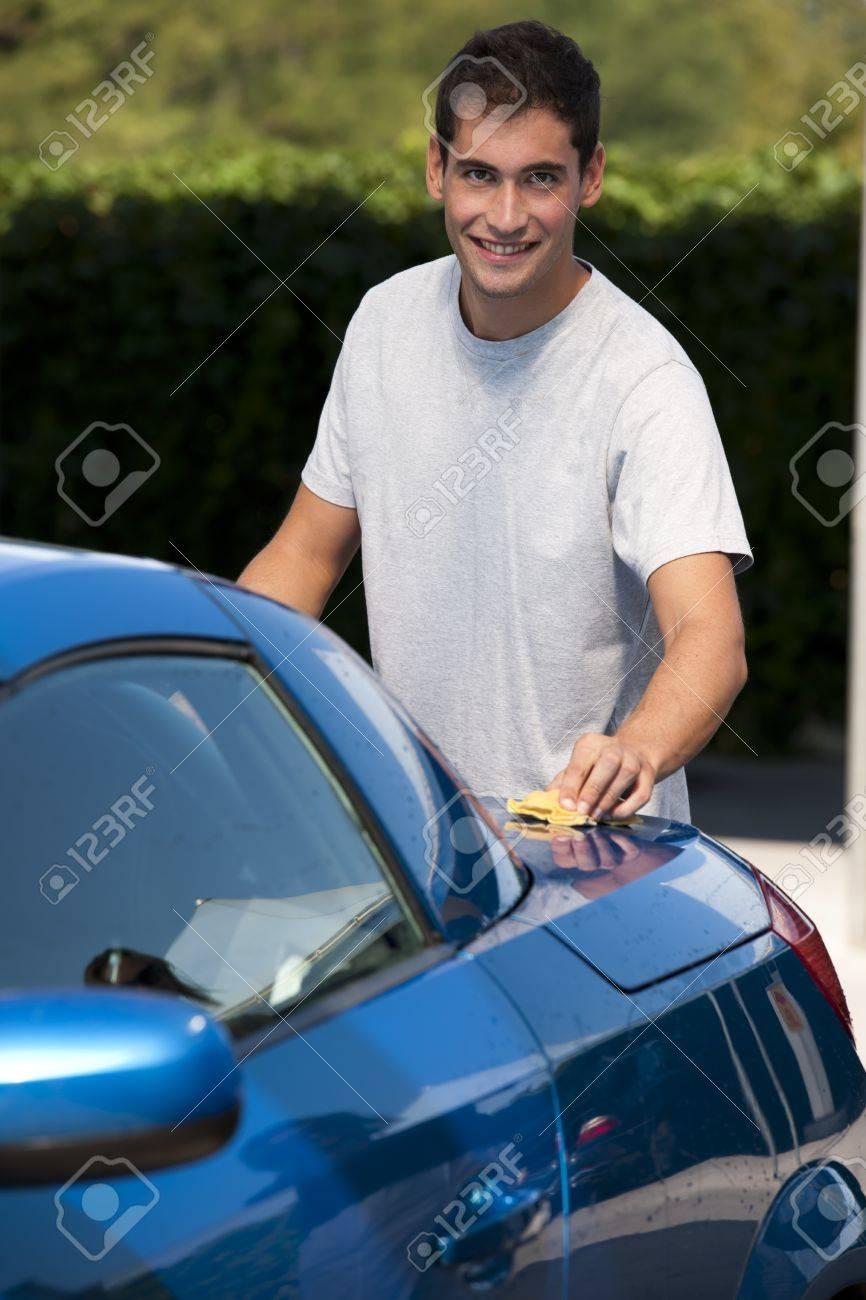 Happy young man cleaning his car with sponge Stock Photo - 12967932