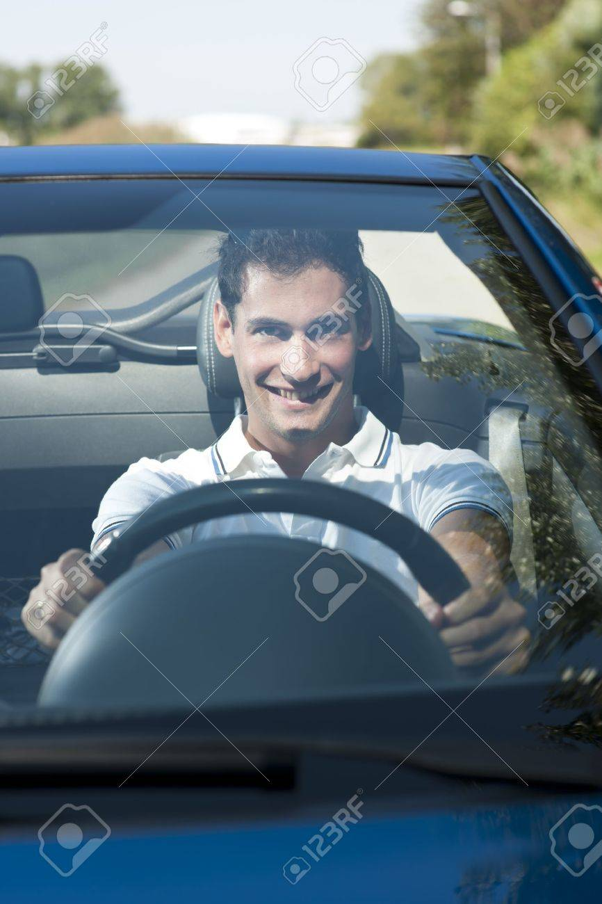 Front view of a young man driving his convertible car - 12967848