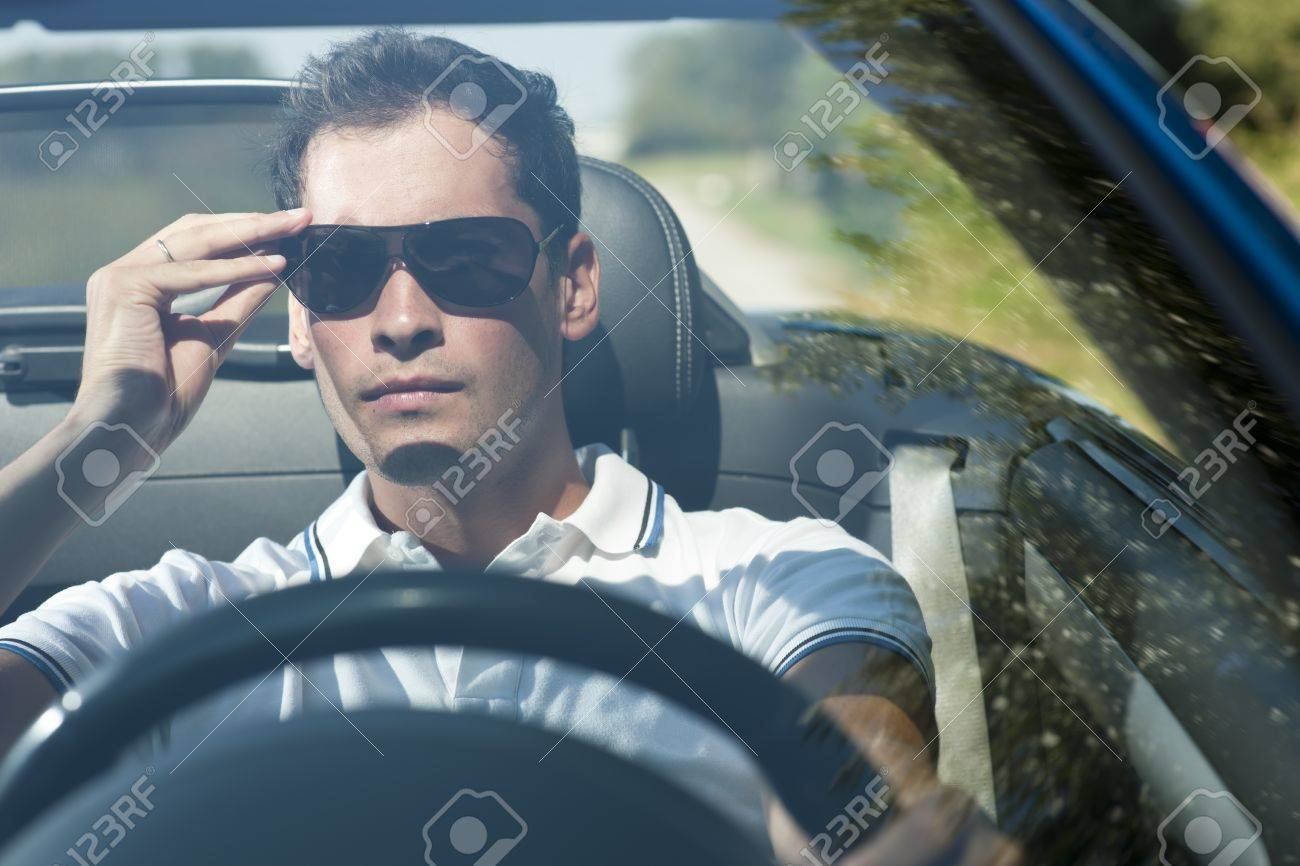 Front View Of A Young Man Driving His Convertible Car Stock Photo   13036119