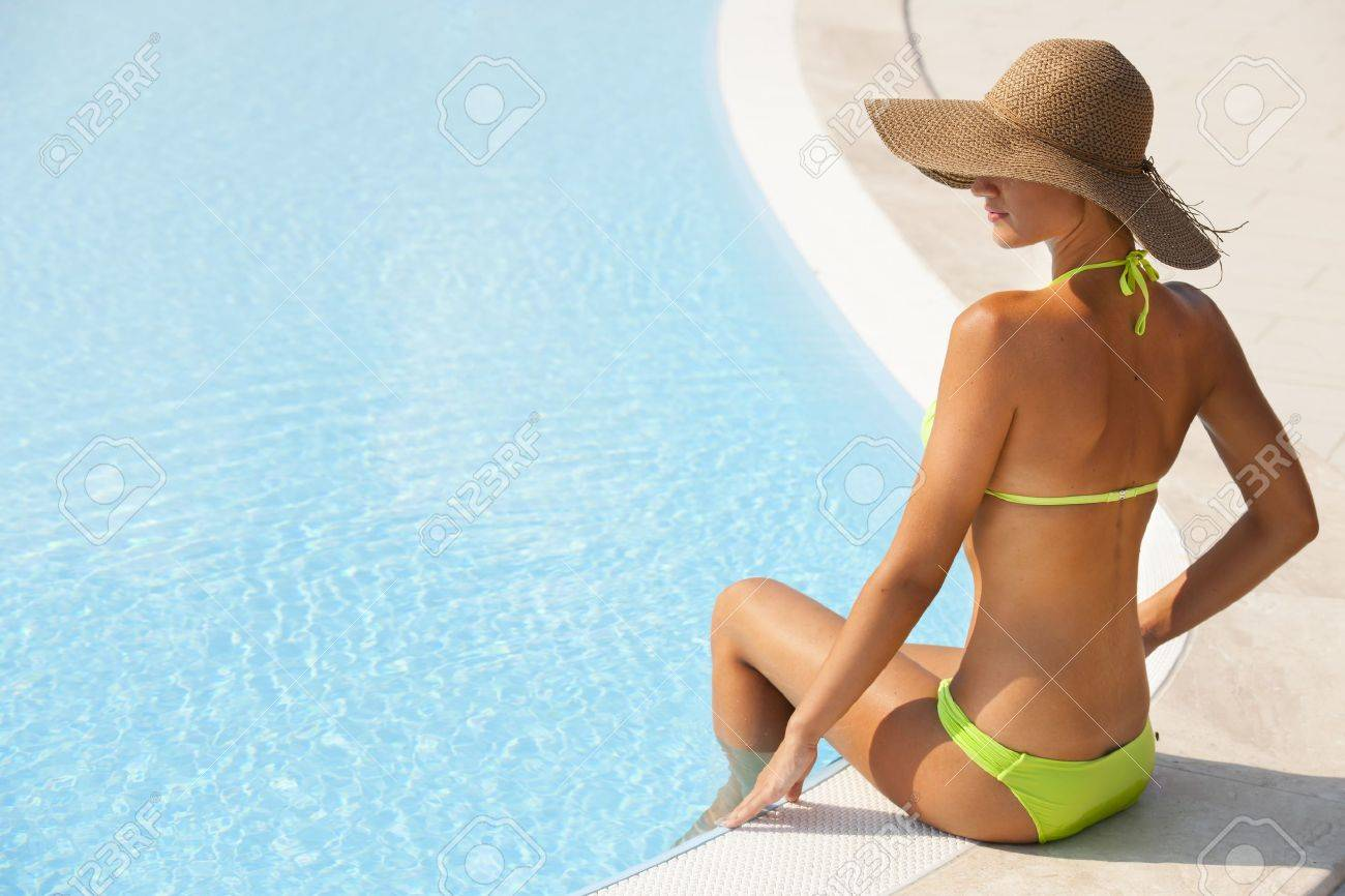Beautiful young woman sitting by swimming-pool, lots of copy-space Stock Photo - 13245058