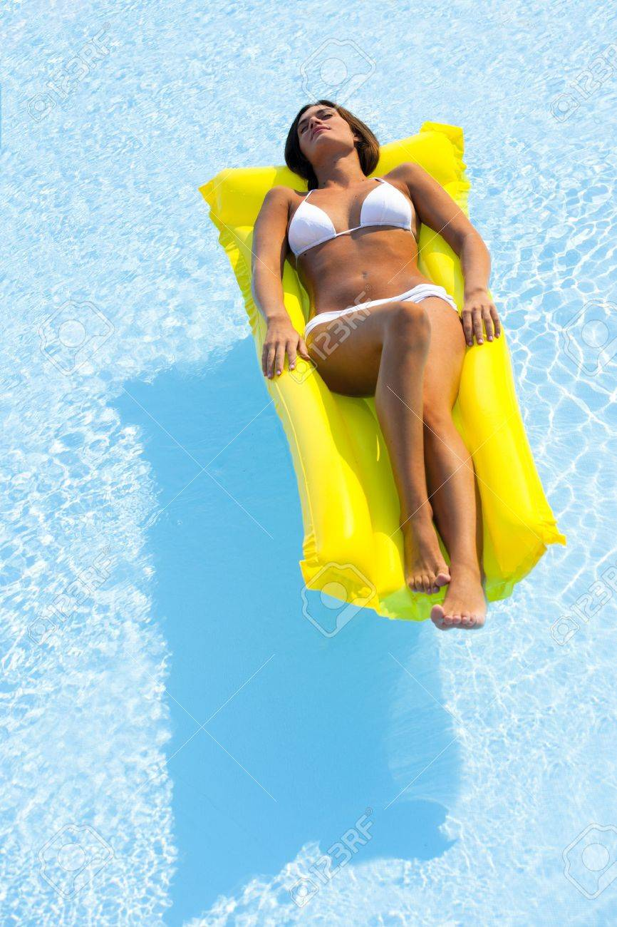 Beautiful woman relaxing and floating on pool, high angle view Stock Photo - 13245334