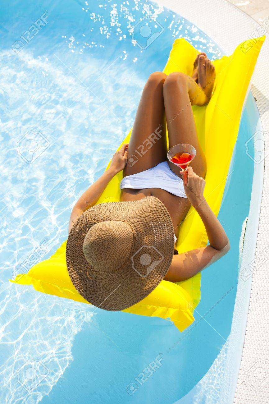 Young woman relaxing on pool with drink - 13245083