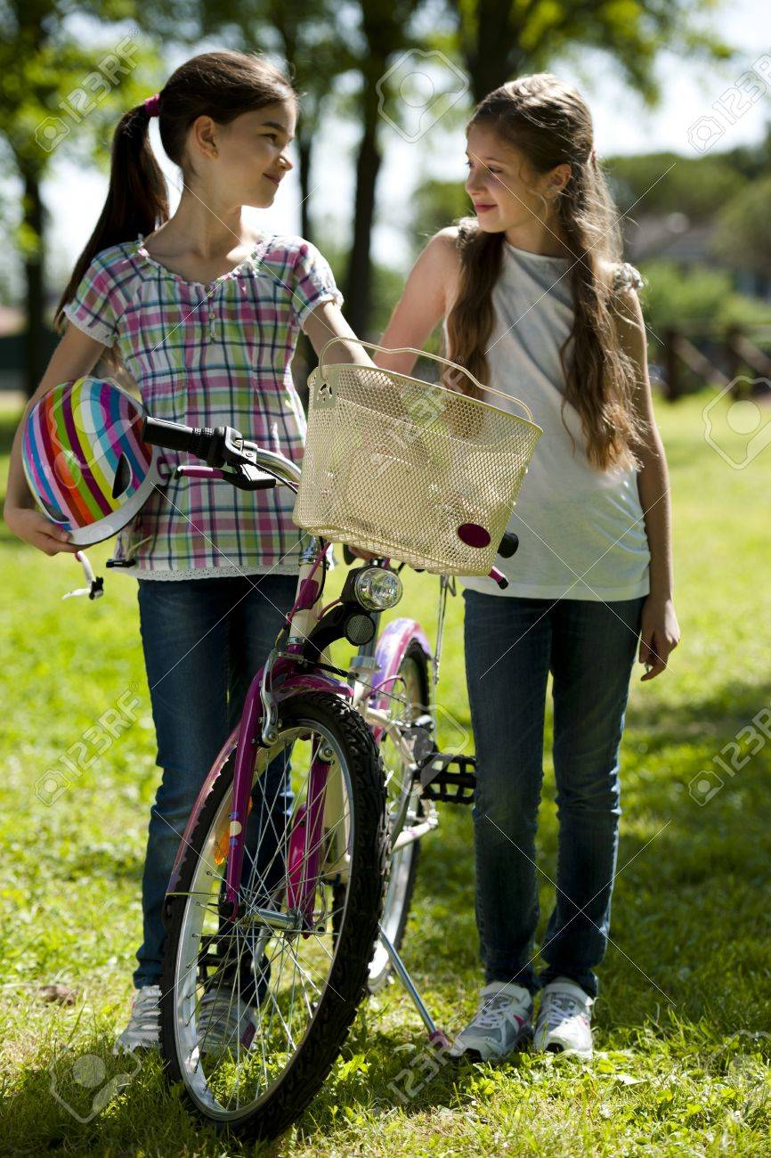 Two little girls with bike outdoors - 15455464