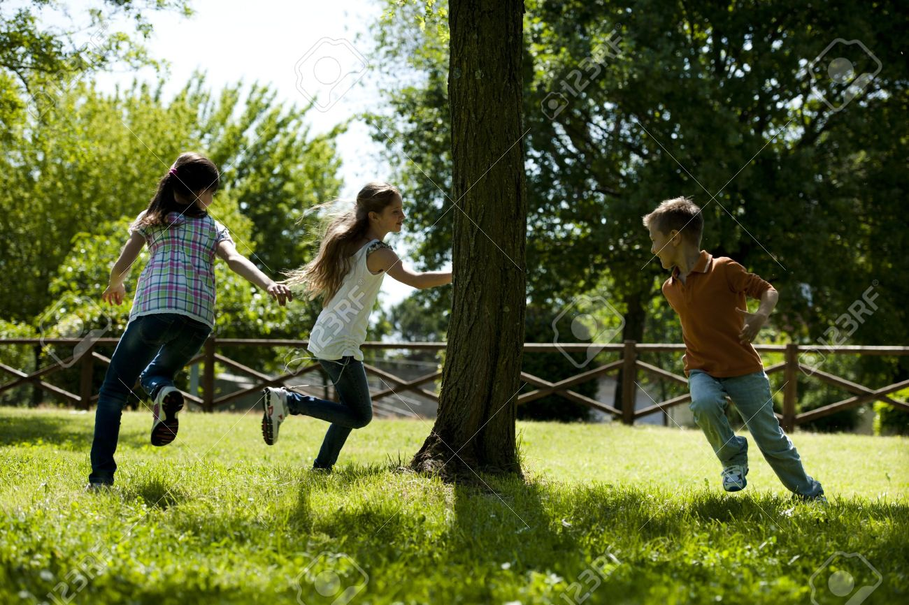 Small group of children playing running around a tree, playing tag - 15455469