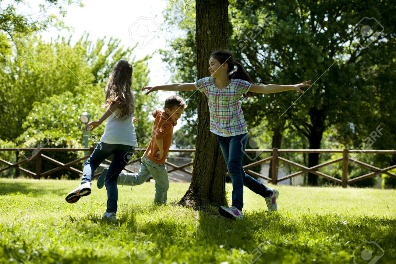 Small group of children playing running around a tree, playing tag - 15455472