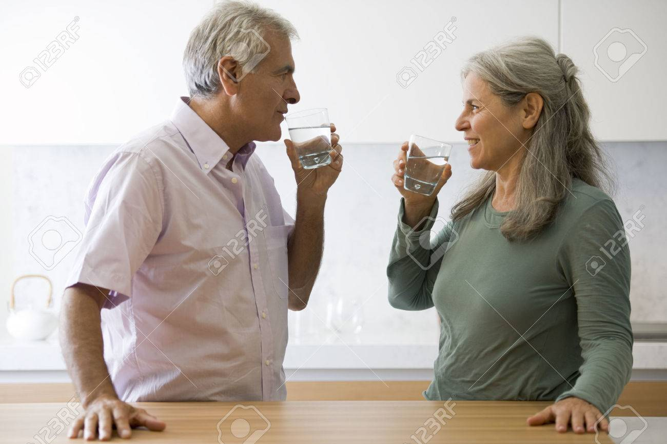 Senior couple drinking water in the kitchen - 27341791