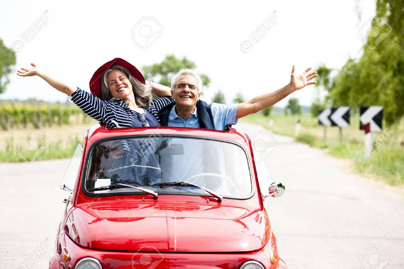 Happy senior couple driving vintage car - 31558269
