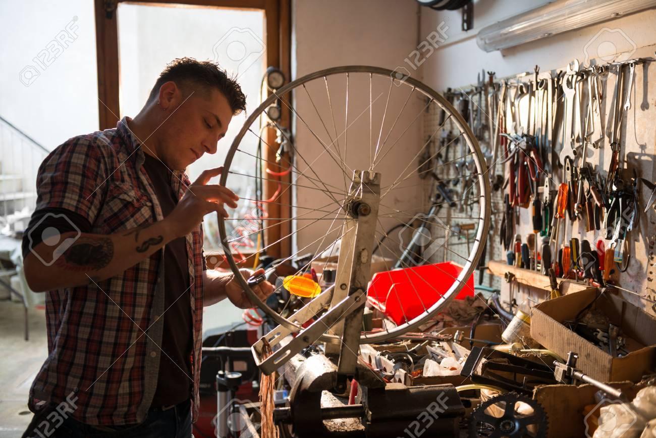 Young man working in a biking repair shop - 31076967