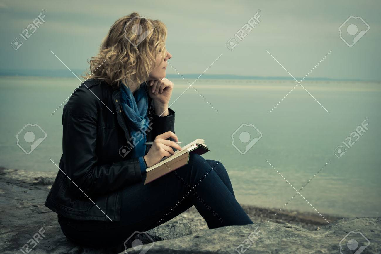 Woman writing her thoughts or poetry by the sea - 31077045