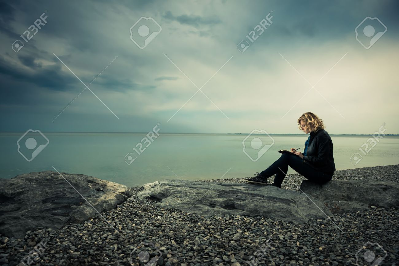 Woman writing her thoughts or poetry by the sea - 31077052